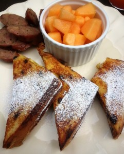 Fresh Orange Infused French Toast with Warm Maple Syrup, Sausage and Honey-Tossed Melon.